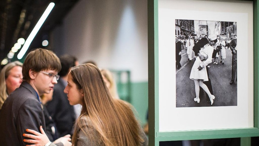 "FILE - In this April 14, 2015 file photo, people speak next to a famous photograph taken by Alfred Eisenstaedt of a sailor kissing a nurse in New York's Times Square on V-J Day, right, as they visit the exhibition of German-American ""Life"" magazine photographer Alfred Eisenstaedt at Moscow's Jewish Museum and Tolerance Center in Moscow, Russia. The woman who was kissed by an ecstatic sailor in Times Square celebrating the end of World War II has died at the age of 92. Greta Zimmer Friedman's son says his mother died Thursday, sept. 8, 2016, at a hospital in Richmond, Virginia. She died from complications of old age, he said. (AP Photo/Alexander Zemlianichenko, File)"