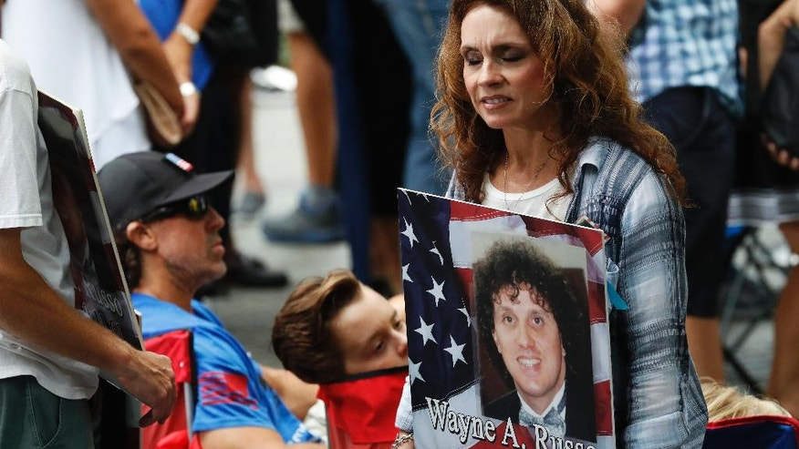 A mourner holds a photo of her loved one during the 15th anniversary of the attacks of the World Trade Center at the National September 11 Memorial, Sunday, Sept. 11, 2016, in New York. (AP Photo/Mary Altaffer)