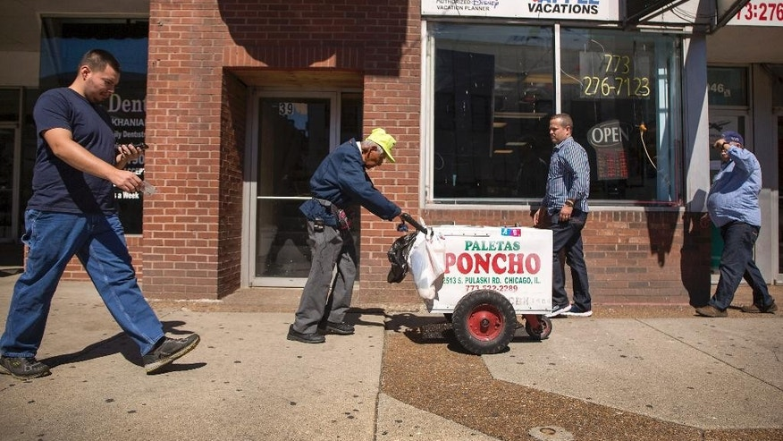 Fidencio Sanchez pushes his cart down the street, Monday, Sept.12, 2016, in Chicago.  What began as a small effort to help out Sanchez, who was spotted pushing a paleta cart and selling the frozen treats to help pay bills has brought in more than $250,000 in just four days.  (Alyssa Pointer/Chicago Tribune via AP)