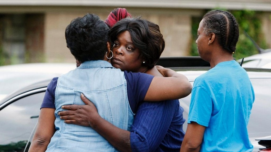 Pastor Mary Moore, left, hugs a woman outside a home where an early morning fire killed multiple people, including children, Monday, Sept. 12, 2016, in Memphis, Tenn. (AP Photo/Karen Pulfer Focht)
