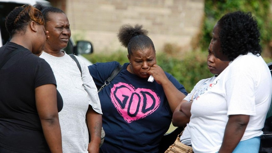 Nichole Mitchell, center, stands with friends outside a home where an early morning fire killed multiple people, including children, Monday, Sept. 12, 2016, in Memphis, Tenn. Mitchell said she is a friend of the family that lived in the home. (AP Photo/Karen Pulfer Focht)