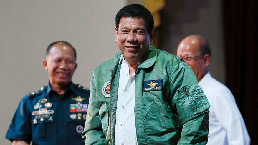 """Philippine President Rodrigo Duterte, center, smiles as he is presented with a pilot's jacket during his """"Talk with the Airmen"""" on the anniversary of the 250th Presidential Airlift Wing Tuesday, Sept. 13, 2016 at the Philippine Air Force headquarters in suburban Pasay city, southeast of Manila, Philippines. On Monday, President Duterte, in his first public statement opposing the presence of American troops, said he wants U.S. forces out of his country's south and blamed the United States for inflaming Muslim insurgencies in the region. (AP Photo/Bullit Marquez)"""