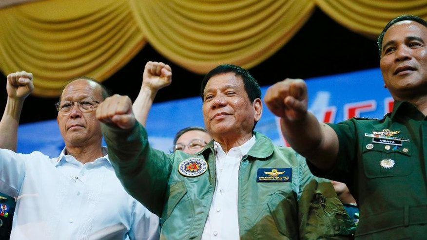 """Philippine President Rodrigo Duterte, center, poses with a fist bump with Defense Chief Delfin Lorenzana, left, and Armed Forces Chief Ricardo Visaya during his """"Talk with the Airmen"""" on the anniversary of the 250th Presidential Airlift Wing, Tuesday, Sept. 13, 2016 at the Philippine Air Force headquarters in suburban Pasay city, southeast of Manila, Philippines. On Monday, President Duterte, in his first public statement opposing the presence of American troops, said he wants U.S. forces out of his country's south and blamed the United States for inflaming Muslim insurgencies in the region. (AP Photo/Bullit Marquez)"""