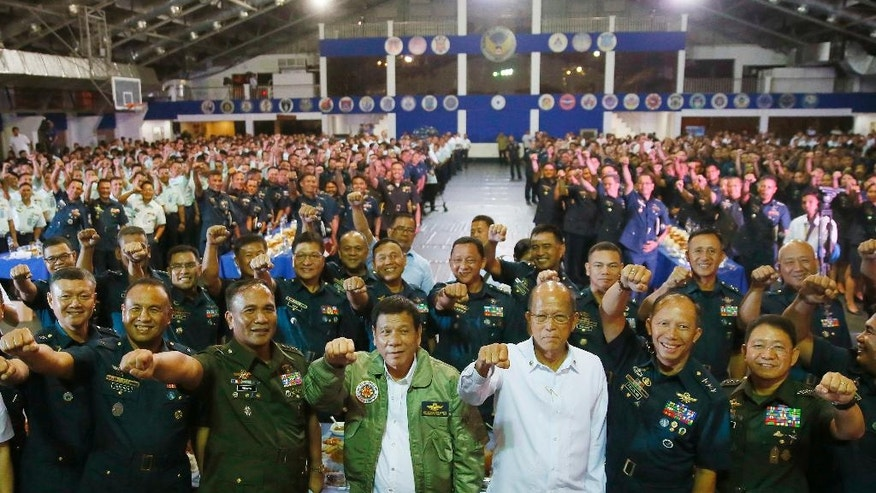 "Philippine President Rodrigo Duterte, center, poses with a fist bump with Defense Chief Delfin Lorenzana, third from right, and Armed Forces Chief Ricardo Visaya, third from left, during his ""Talk with the Airmen"" on the anniversary of the 250th Presidential Airlift Wing, Tuesday, Sept. 13, 2016, at the Philippine Air Force headquarters in suburban Pasay city, southeast of Manila, Philippines. On Monday, President Duterte, in his first public statement opposing the presence of American troops, said he wants U.S. forces out of his country's south and blamed the United States for inflaming Muslim insurgencies in the region. (AP Photo/Bullit Marquez)"