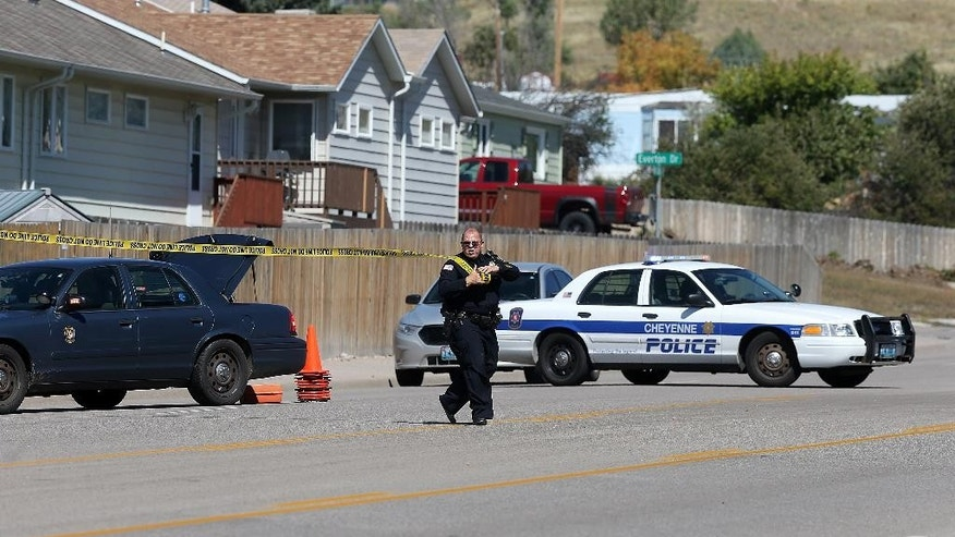 A Cheyenne police officer tapes off North College Drive after a shooting at Heritage Court Apartments Wednesday, Sept. 14, 2016 in northeast Cheyenne, Wyo.  A 77-year-old man living at a senior citizen apartment complex shot three people at the complex Wednesday, killing one of them, and then killed himself nearby as officers closed in on him, police said. (Blaine McCartney/The Wyoming Tribune Eagle via AP)