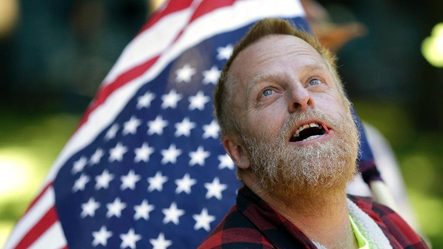 A protester carries an upside down American flag as he looks up at the federal courthouse in Portland, Ore., Tuesday, Sept. 13, 2016.  Opening statements are set to begin Tuesday in the trial of the Bundy brothers, Ammon and Ryan, and five others who occupied a remote bird sanctuary in Oregon's high desert early this year. The standoff drew national attention to the decades-old fight between the federal government and Western states over land policy.  (AP Photo/Don Ryan)