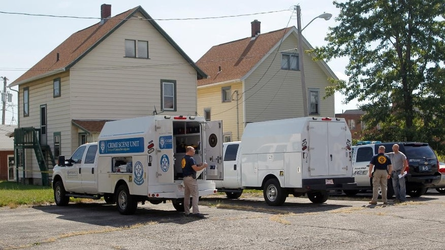 Ashland Police Department and Ohio BCI execute a search warrant on a home on Tuesday, Sept. 13, 2016, in Ashland, Ohio. Authorities say a woman reported being held captive, leading to the arrest of a kidnapping suspect, a murder confession and the discovery of three bodies. Two bodies were found Tuesday at a home in Ashland. The third was found in nearby Madison Township.  (Tom E. Puskar/The Times Gazette via AP)