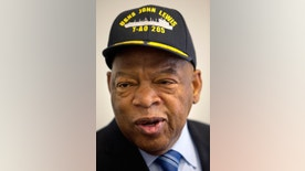 FILE - In this Jan. 6, 2016 file photo, Rep. John Lewis, D-Ga., wears a hat bearing the name of a fleet replenishment oiler named after him during a ceremony with Navy Secretary Ray Mabus on Capitol Hill in Washington. Mabus has raised a few eyebrows with some of the names he has picked for naval ships. Mabus is officially announcing five new ship names on visits to Mississippi and Massachusetts beginning Saturday, Sept. 17. (AP Photo/Jacquelyn Martin, File)