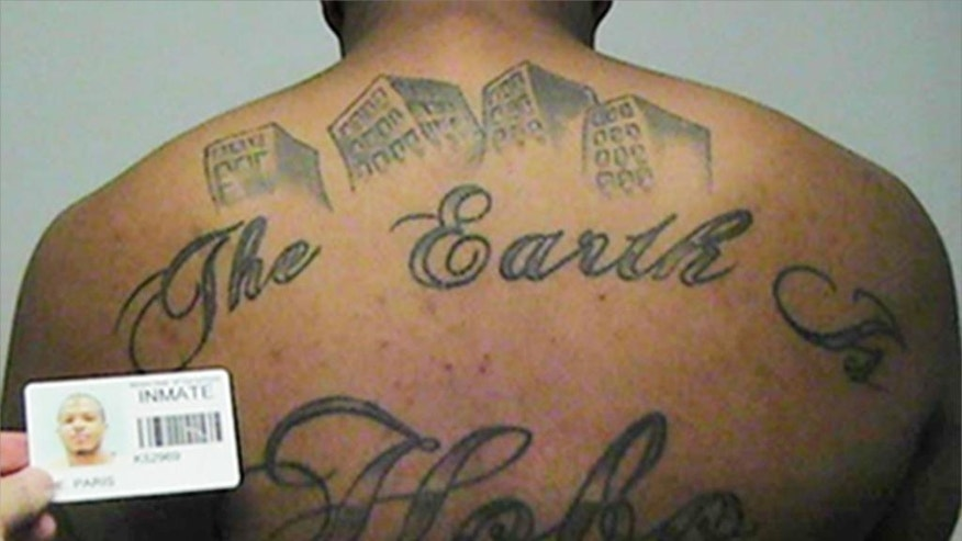 This undated photo in a court filing provided by the United States Attorney's office in Chicago, shows Paris Poe's back tattoo that reads 'The Earth Is Our Turf, and Hobo. Poe is one of six defendants on trial for racketeering and other charges are purported leaders of the widely feared Hobos, a South Side gang that federal prosecutors say murdered, maimed and tortured their way into control of some of Chicago's most lucrative drug markets. Their federal trial begins Wednesday, Sept. 14, 2016 with opening statements in Chicago. (United States Attorney's office in Chicago via AP)
