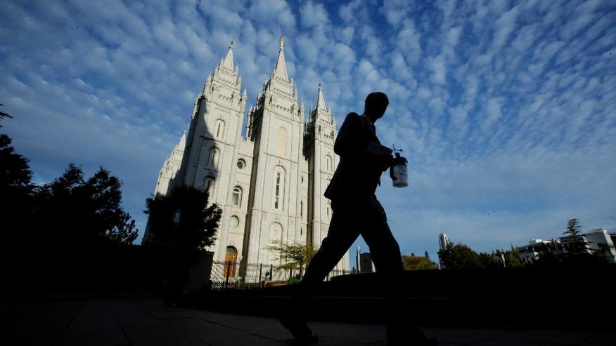 A man walks past the Salt Lake Temple,  a temple of The Church of Jesus Christ of Latter-day Saints, at Temple Square, Wednesday, Sept. 14, 2016, in Salt Lake City. The Pew Research Center survey found that just under half of Mormon registered voters, 48 percent, describe themselves as Republican this year. That's down from 61 percent four years ago when Mitt Romney was the party's presidential nominee. (AP Photo/Rick Bowmer)