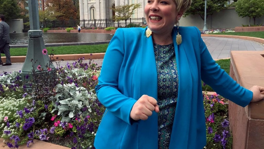 Crystal Young-Otterstrom, vice chair of the LDS Democrats of America, stands in front of the Salt Lake Temple, a temple of The Church of Jesus Christ of Latter-day Saints, at Temple Square, Wednesday, Sept. 14, 2016, in Salt Lake City. The Pew Research Center survey found that just under half of Mormon registered voters, 48 percent, describe themselves as Republican this year. That's down from 61 percent four years ago when Mitt Romney was the party's presidential nominee. (AP Photo/Brady McCombs)