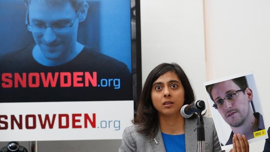 Naureen Shah, director of Amnesty International USA's Security & Human Rights Program, holds up a photo of Edward Snowden during a news conference to call upon President Barack Obama to pardon Snowden before he leaves office, Wednesday, Sept. 14, 2016, in New York. Human and civil rights organizations, including the ACLU, Human Rights Watch and Amnesty International, launched a public campaign to persuade Obama to pardon the former National Security Agency contractor, who leaked classified details in 2013 of the U.S. government's warrantless surveillance program before fleeing to Russia.  (AP Photo/Mary Altaffer)