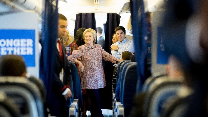 Democratic presidential candidate Hillary Clinton smiles as she speaks to aids on her campaign plane, in White Plains, N.Y., Thursday, Sept. 15, 2016, before traveling to Greensboro, N.C. for a rally. Clinton returned to the campaign trail after a bout of pneumonia that sidelined her for three days and revived questions about both Donal Trump's and her openness regarding their health. (AP Photo/Andrew Harnik)