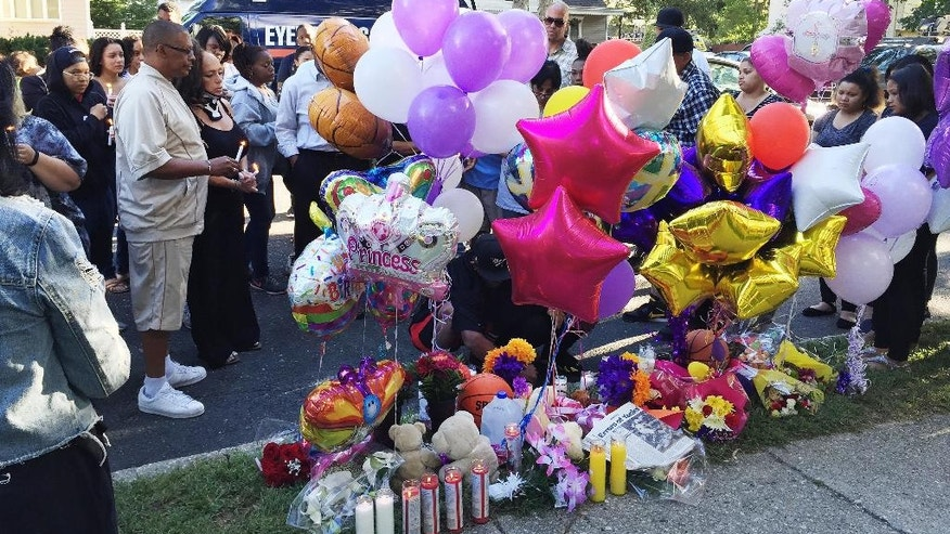 In this Sept. 15, 2016 photo, family members, friends and community members gather for a vigil in Brentwood, N.Y. at a memorial near the scene where Nisa Mickens and Kayla Cuevas were found dead.  Police say the teens may have died together. The badly beaten bodies of both girls, ages 15 and 16, were discovered in their suburban neighborhood this week. (AP Photo/Mike Balsamo)