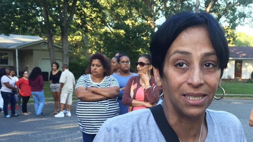 In this Sept. 15, 2016 photo, Evelyn Cuevas, the mother of Kayla Cuevas, speaks with reporters in Brentwood, N.Y. near the scene where her daughter was found dead.  The badly beaten bodies of Kayla Cuevas and Nisa Mickens were discovered in their suburban neighborhood this week. (AP Photo/Mike Balsamo)