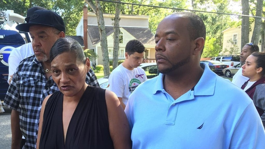 In this Sept. 15, 2016 photo, Elizabeth Alvarado and Rob Mickens speak with reporters at the scene where their daughter, Nisa Mickens, was found dead in Brentwood, N.Y.   The badly beaten bodies of Kayla Cuevas and Nisa Mickens were discovered in their suburban neighborhood this week. (AP Photo/Mike Balsamo)