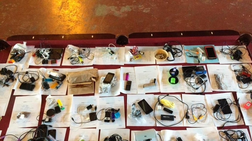In this photo provided by the Oklahoma Department of Corrections, cellphones and electronic devices confiscated from the Center Point halfway house are pictured in Oklahoma City. Friday, Sept. 16, 2016. Officials seized 18 cellphones, 87 phone chargers, 39 syringes, marijuana and methamphetamine. (Oklahoma Department of Corrections via AP)