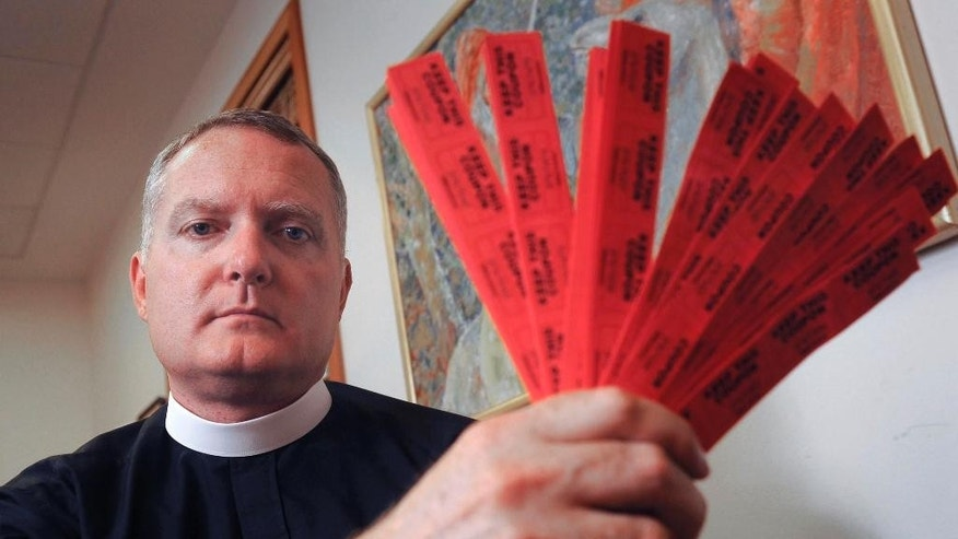 FILE--In this July 27, 2016, file photo, Rev. Jeremy Lucas of Christ Church Episcopal Parish holds the 150 tickets that he purchased in an all-star softball team's raffle to win an AR-15 assault rifle in Lake Oswego, Ore. Authorities have decided Lucas won't be charged for giving the assault rifle to a gun-owning friend for safekeeping without a background check, Thursday, Sept. 15, 2016. (Vern Uyetake/Lake Oswego Review via AP, File)