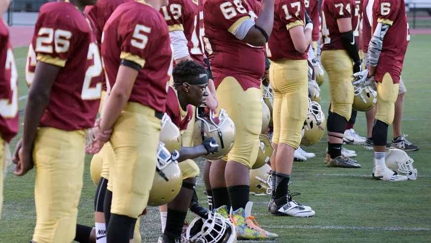 Doherty High School football player Michael Oppong kneels during the national anthem before the team's high school football game against Leominster in Worcester, Mass., Sept 9, 2016.