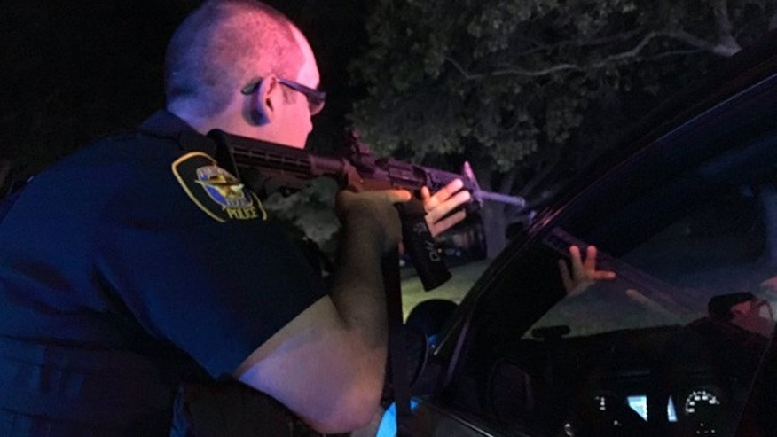 Sept. 16, 2016: A Fort Worth police officer draws his gun at the scene of a shooting that injured two officers.