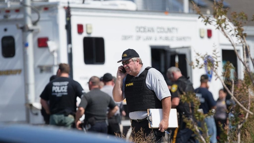 Police gather at a command center in Seaside Park, N.J., on Saturday, Sept. 17, 2016, during an investigation of a pipe bomb which exploded before a charity race to benefit Marines and sailors. No injuries were reported. (Peter Ackerman/The Asbury Park Press via AP)