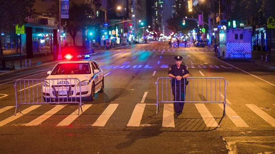 Police stand guard as the cordon Sixth Avenue near the scene of Saturday's explosion on West 23rd Street and Sixth Avenue in Manhattan's Chelsea neighborhood, New York, Sunday, Sept. 18, 2016. An explosion rocked the block of West 23rd Street between Sixth and Seventh Avenues at 8:30 p.m. Saturday. Officials said more than two dozen people were injured. Most of the injuries were minor. (AP Photo/Andres Kudacki)