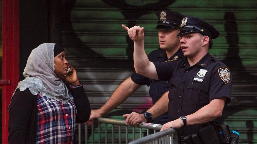 A woman tries to access to the area near the scene of Saturday's explosion on West 23rd Street and Sixth Avenue in Manhattan's Chelsea neighborhood, ass police stand guard in New York, Sunday, Sept. 18, 2016. An explosion rocked the block of West 23rd Street between Sixth and Seventh Avenues at 8:30 p.m. Saturday. Officials said more than two dozen people were injured. Most of the injuries were minor. (AP Photo/Andres Kudacki)