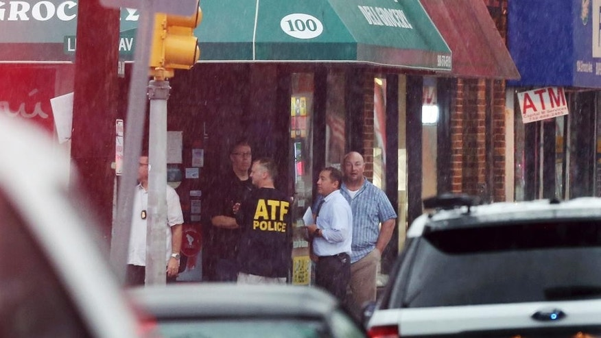 Police and officials gather in the doorway of a building early Monday, Sept. 19, 2016, in Elizabeth, N.J. A suspicious device found in a trash can near a train station exploded early Monday as a bomb squad was attempting to disarm it with a robot, officials said. (AP Photo/Mel Evans)
