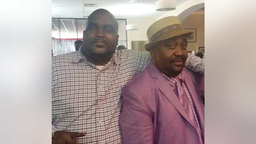 This undated photo provided by the Parks & Crump, LLC shows Terence Crutcher, left, with his father, Joey Crutcher. Crutcher, an unarmed black man was killed by a white Oklahoma officer Friday, Sept. 16, 2016, who was responding to a stalled vehicle. (Courtesy of Crutcher Family/Parks & Crump, LLC via AP)