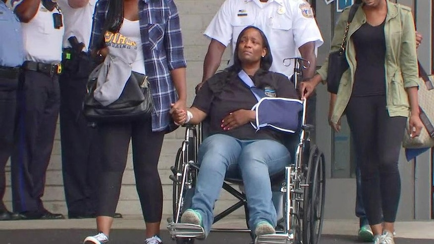 In this image from video provided by WTXF Fox Philadelphia, Philadelphia Police Department Sgt. Sylvia Young is saluted by dozens of uniformed police officers Tuesday, Sept. 20, 2016, as she's discharged from Penn Presbyterian Medical Center in Philadelphia. Authorities say Nicholas Glenn ambushed Philadelphia Police Department Sgt. Sylvia Young in her patrol car Friday, Sept. 16, 2016, and then killed 25-year-old Sara Salih and wounded University of Pennsylvania police officer Ed Miller, before Glenn was shot and killed by other officers in an alley. (AP Photo/WTXF Fox Philadelphia)