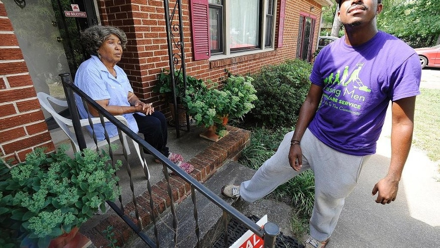 In this photo taken Saturday, Sept. 10, 2016 in Huntsville, Ala., Rodney Smith Jr., founder of Raising Men Lawn Care Service, looks skyward while talking with homeowner Irene Renee Jolly, 77. Founded last year, Smith's group is providing free lawn care for about 100 yards a month. His goal is to help the elderly, disabled, single mothers and veterans. Young people also participate and learn about the importance of volunteering. (AP Photo/Jay Reeves)
