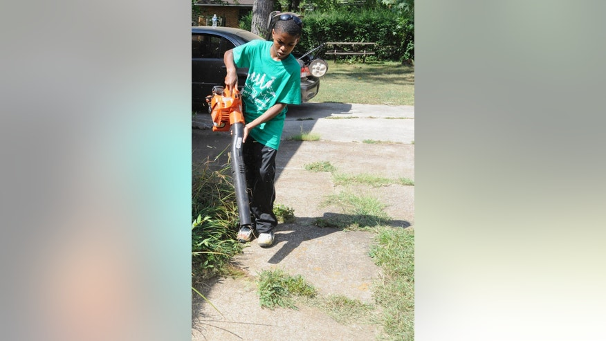 In this photo taken Saturday, Sept. 10, 2016, in Huntsville, Ala., 13-year-old Jarius Smith cleans a homeowner's walkway while volunteering for Raising Men Lawn Care Service. Founded last year, the service provides free yard care for the elderly, disabled, single mothers and veterans. Parents sign up youngsters to participate to teach them about volunteering. (AP Photo/Jay Reeves)