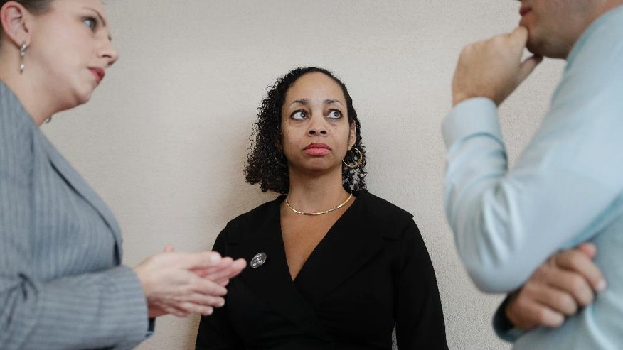 """Erika Ballou, a deputy public defender in Clark County, Nev., speaks with colleagues outside of a courtroom Tuesday, Sept. 20, 2016, in Las Vegas. Ballou sparked a protest in a Las Vegas courtroom where she refused on Tuesday to remove a """"Black Lives Matter"""" button from her blouse despite a judge's request not to demonstrate what he called """"political speech."""" (AP Photo/John Locher)"""