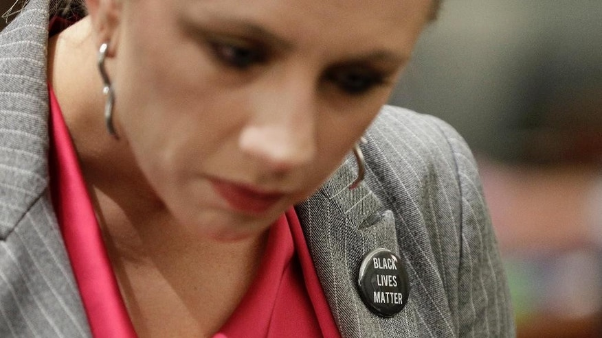 """Sarah Hawkins, a deputy public defender in Clark County, Nev., wears a """"Black Lives Matter"""" pin in support of fellow public defender Erika Ballou in a courtroom Tuesday, Sept. 20, 2016, in Las Vegas. Ballou sparked a protest in a Las Vegas courtroom where she refused on Tuesday to remove a """"Black Lives Matter"""" button from her blouse despite a judge's request not to demonstrate what he called """"political speech."""" (AP Photo/John Locher)"""