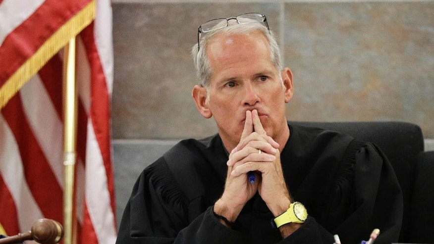 """Judge Douglas W. Herndon listens to Erika Ballou, a deputy public defender in Clark County, Nev., in a courtroom Tuesday, Sept. 20, 2016, in Las Vegas. Ballou sparked a protest in a Las Vegas courtroom where she refused on Tuesday to remove a """"Black Lives Matter"""" button from her blouse despite a Herndon's request not to demonstrate what he called """"political speech."""" (AP Photo/John Locher)"""