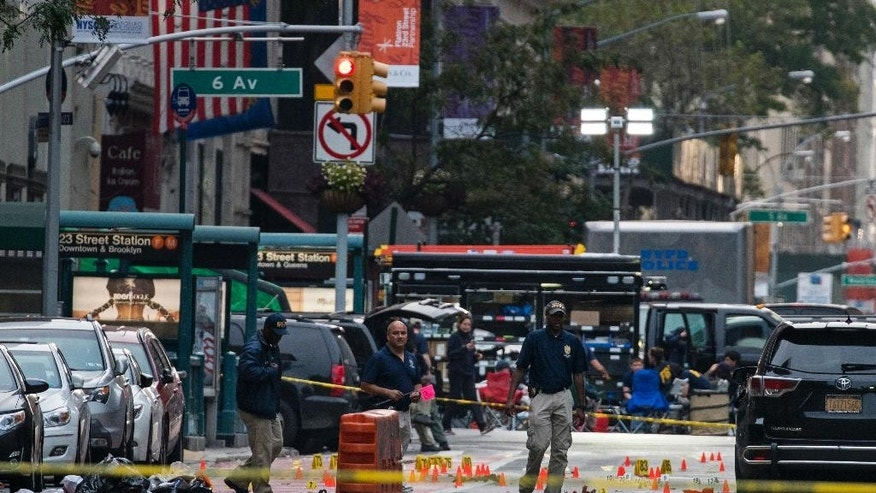 FILE- In this Sept. 18, 2016 file photo, crime scene investigators work the scene of a pressure cooker bomb explosion in Manhattan's Chelsea neighborhood, in New York. Although the device that wounded over two dozen people on the street went off in front of an apartment building for the blind, none of the building's residents were hurt in the blast. (AP Photo/Craig Ruttle, File)