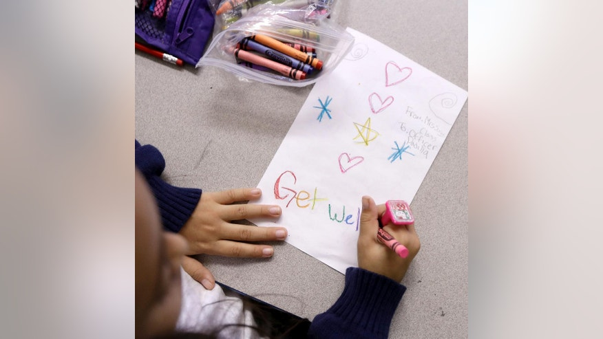 Arianna Cestona, a third grade student at Linden School No. 5, makes a card for Linden Police officer Angel Padilla, Thursday, Sept. 22, 2016, in Linden, N.J. Padilla, who was injured in a shootout with the man suspected of setting off bombs in the New York City, paid a visit to the school where he is a member of the PTA. Students wrote get well cards for Padilla and officer Pete Hammer, who were both hurt in Monday's shootout with Ahmad Khan Rahami. (AP Photo/Julio Cortez)
