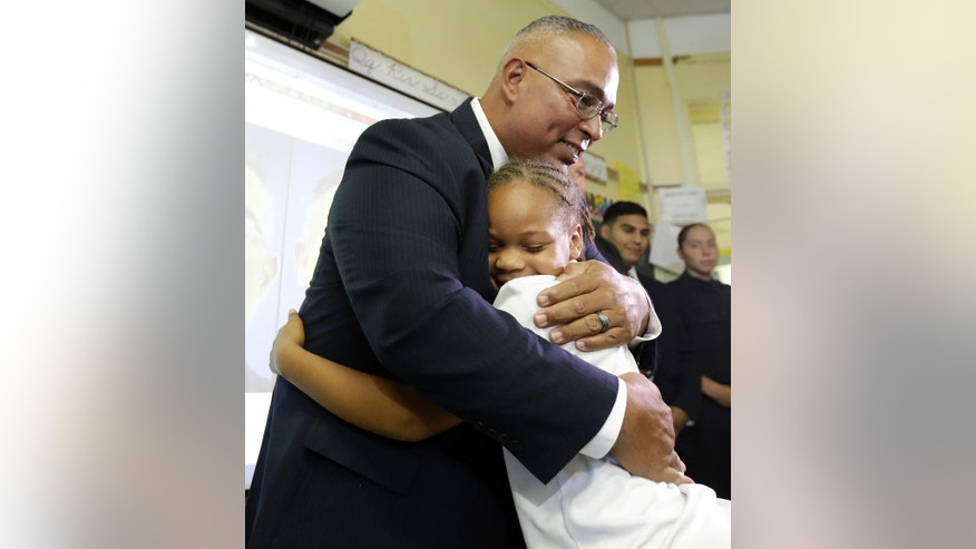 Linden Police officer Angel Padilla, left, is hugged by Mya Austin, a third grade student at Linden School No. 5, during a visit to the school, Thursday, Sept. 22, 2016, in Linden, N.J. Padilla, who was injured in a shootout with Ahmad Khan Rahami, the man suspected of setting off bombs in the New York City, paid a visit to the school where he is a member of the PTA. Students wrote get well cards for Padilla and officer Pete Hammer, who were both hurt in Monday's shootout with Rahami. (AP Photo/Julio Cortez)