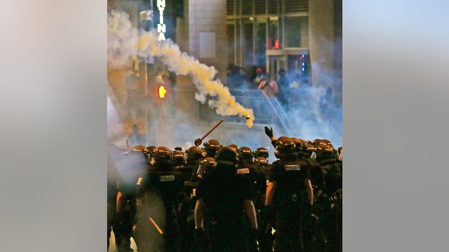 Police fire tear gas as protestors converge downtown following Tuesday's police shooting of Keith Lamont Scott in Charlotte, N.C., Wednesday, Sept. 21, 2016. Protesters have rushed police in riot gear at a downtown Charlotte hotel and officers have fired tear gas to disperse the crowd. At least one person was injured in the confrontation, though it wasn't immediately clear how. Firefighters rushed in to pull the man to a waiting ambulance.(AP Photo/Gerry Broome)