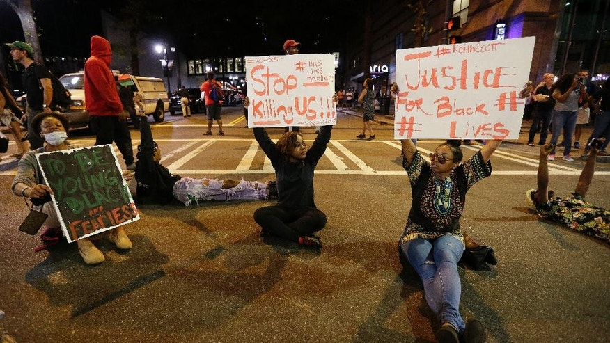 Demonstrators sit on a street during a protest of Tuesday's fatal police shooting of Keith Lamont Scott in Charlotte, N.C. on Wednesday, Sept. 21, 2016. Protesters rushed police in riot gear at a downtown Charlotte hotel and officers have fired tear gas to disperse the crowd. At least one person was injured in the confrontation, though it wasn't immediately clear how. Firefighters rushed in to pull the man to a waiting ambulance. (AP Photo/Chuck Burton)