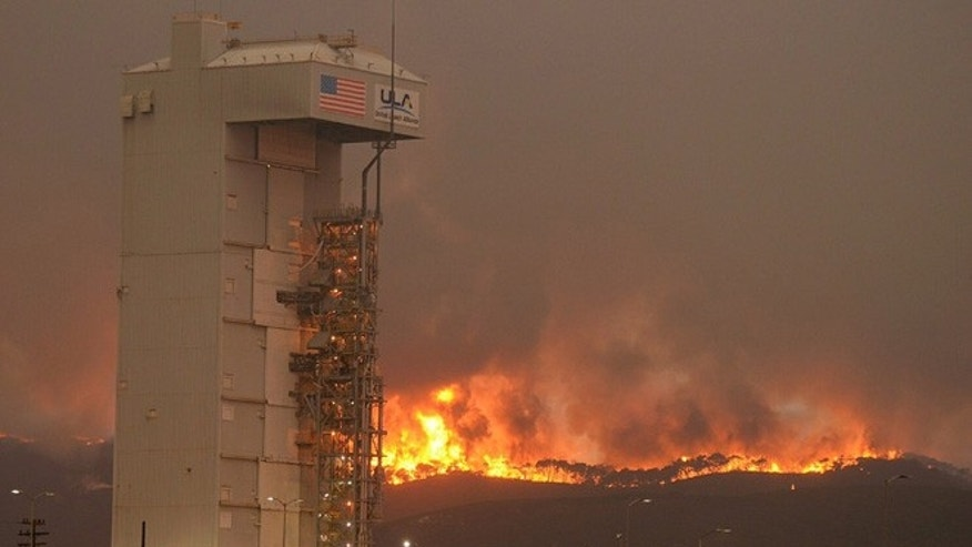 In this Monday, Sept. 19, 2016 photo provided by the Santa Barbara County Fire Department, a fire burns several miles behind Space Launch Complex-3, housing the Atlas V rocket & WorldView 4 satellite, at Vandenberg Air Force Base, Calif.