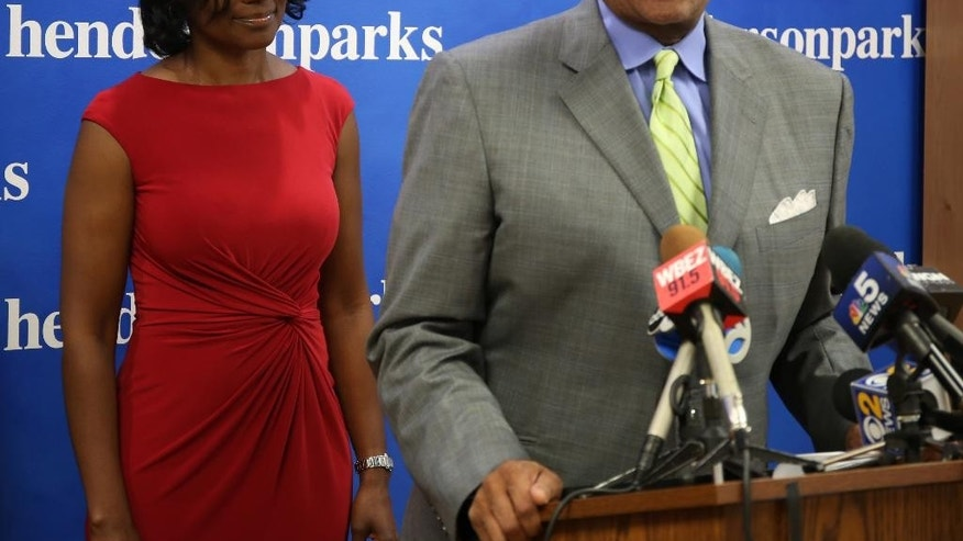 Rhonda Crawford,left,  a court staff attorney fired after donning a robe and hearing real cases on the bench, listens to her lawyer Victor Henderson at a news conference in Chicago on Thursday, Sept.22, 2016.  Crawford says she regrets overseeing several traffic cases. But she says the actual judge, Valarie E. Turner, stood over her the whole time and issued all rulings. Crawford was fired over the incident and Turner was removed from the bench indefinitely. (Phil Velasquez/Chicago Tribune via AP)