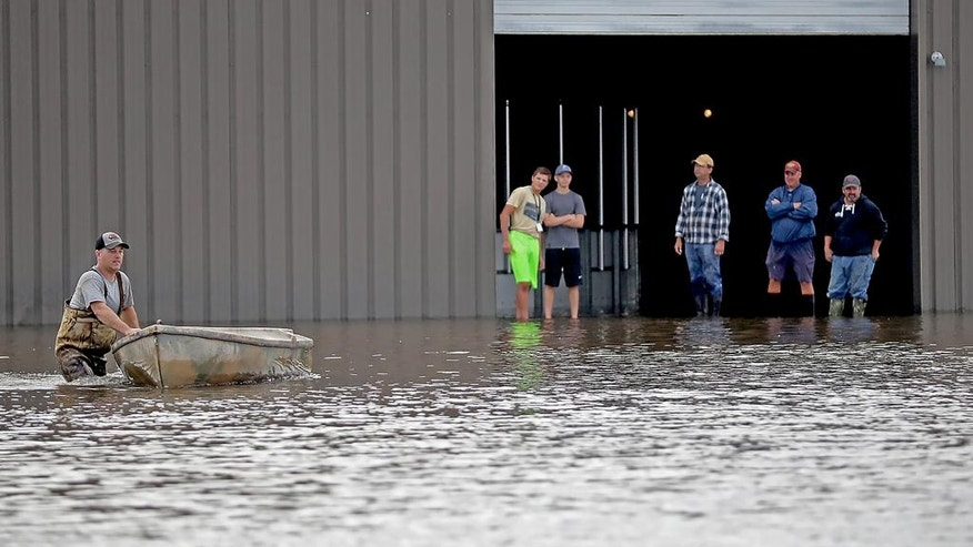 Men stand around to help sand the ice arena near the Waseca High School, Thursday, Sept.  22, 2016 in Waseca, Minn.  Thursday, Sept. 22, 2016. Several Midwestern states were a soggy mess Thursday after up to 10 inches of rain fell in parts of Minnesota, Wisconsin and Iowa.  (Elizabeth Flores/Star Tribune via AP)