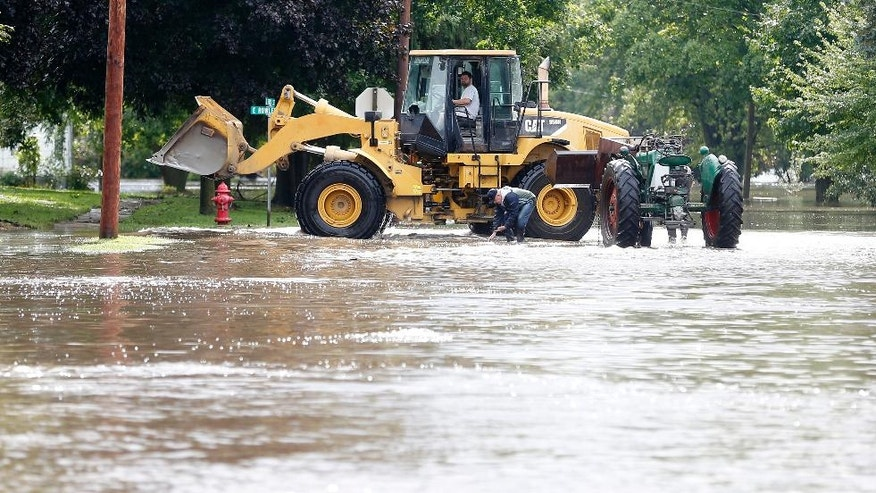 Men move a tractor to higher ground in Greene, Iowa, as the Shell Rock River rises into residential areas Thursday, Sept. 22, 2016. Several Midwestern states were a soggy mess Thursday after up to 10 inches of rain fell in parts of Minnesota, Wisconsin and Iowa.   (Brandon Pollock/The Courier via AP)