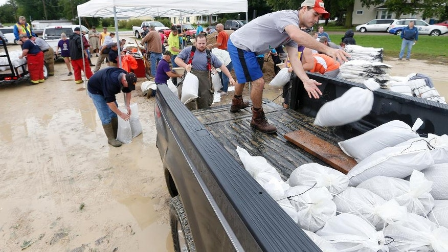Dustin Osier and other volunteers fill sandbags as the Shell Rock River continues to rise in Greene, Iowa, Thursday, Sept. 22, 2016. Several Midwestern states were a soggy mess Thursday after up to 10 inches of rain fell in parts of Minnesota, Wisconsin and Iowa.   (Brandon Pollock/The Courier via AP)