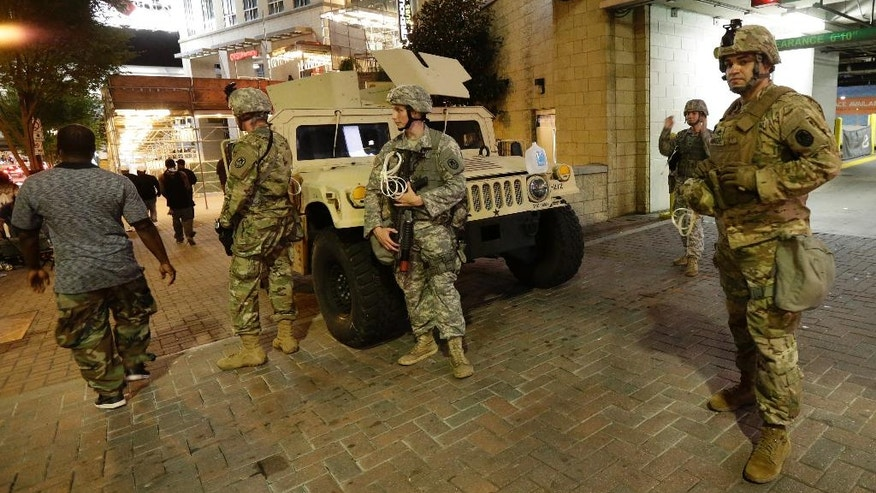 National Guardsman stand on the street in downtown Charlotte, N.C. on Thursday, Sept. 22, 2016. Charlotte police refused under mounting pressure Thursday to release video that could resolve wildly different accounts of the shooting of a black man, as the National Guard arrived to try to head off a third night of violence in this city on edge. (AP Photo/Gerry Broome)