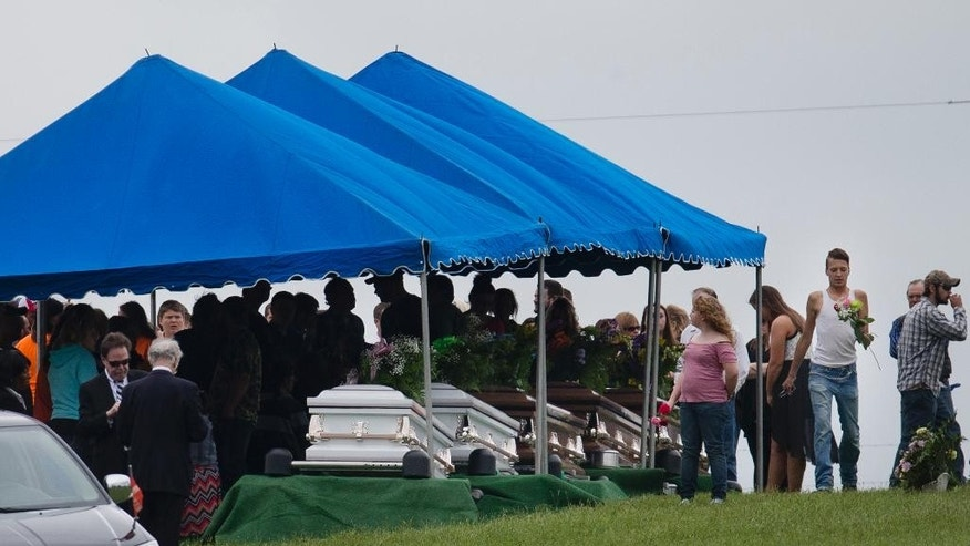 FILE – In this May 3, 2016, file photo, mourners gather around caskets for six of the eight members of the Rhoden family found shot April 22, 2016, at four properties near Piketon, Ohio, during funeral services at Scioto Burial Park in McDermott, Ohio. The office of Ohio Attorney General Mike DeWine released redacted autopsy reports Friday, Sept. 23, in the unsolved slayings of the seven adults and a teenage boy, confirming all but one victim was shot multiple times in the head. (AP Photo/John Minchillo, File)