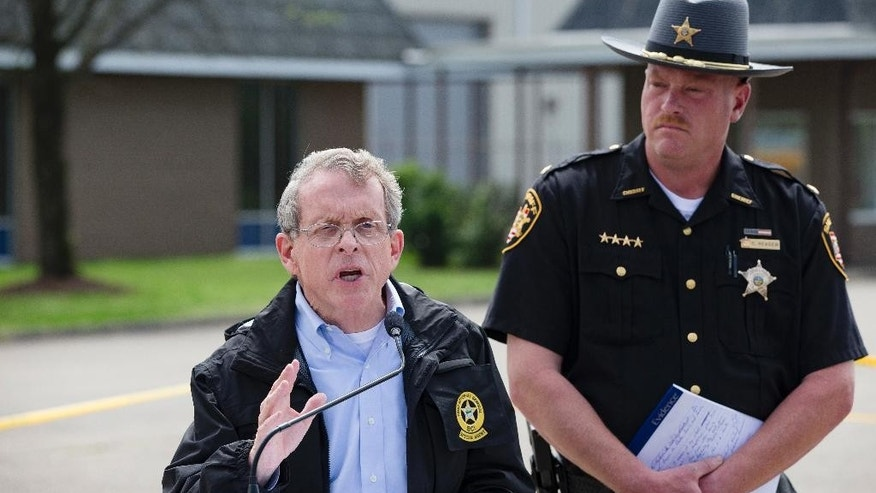 FILE - In this April 27, 2016, file photo, Ohio Attorney General Mike DeWine, left, and Pike County Sheriff Charles Reader, right, discuss the slayings of eight members of the Rhoden family found shot April 22, 2016, at four properties near Piketon, Ohio, during a news conference in Waverly, Ohio. The office of DeWine released redacted autopsy reports Friday, Sept. 23 in the unsolved slayings of the seven adults and a teenage boy, confirming all but one victim was shot multiple times in the head. (AP Photo/John Minchillo, File)