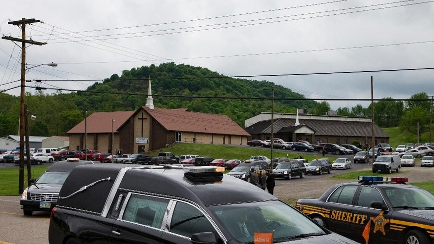FILE – In this May 3, 2016, file photo, hearses for six of the eight members of the Rhoden family found shot April 22, 2016, at four properties near Piketon, Ohio, depart during funeral services from Dry Run Church of Christ in West Portsmouth, Ohio. The office of Ohio Attorney General Mike DeWine released redacted autopsy reports Friday, Sept. 23  in the unsolved slayings of the seven adults and a teenage boy, confirming all but one victim was shot multiple times in the head. (AP Photo/John Minchillo, File)