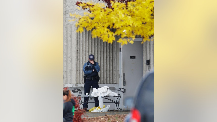 A Burlington Police Dept. officer stands guard at a side entrance to the Macy's department store at the Cascade Mall, Saturday, Sept. 24, 2016, in Burlington, Wash.  Authorities said Saturday several people were dead after the shooting Friday night and the suspect was still at large. The identity of the suspect, his motive and how he got a rifle into the mall remained unanswered. (AP Photo/Ted S. Warren)
